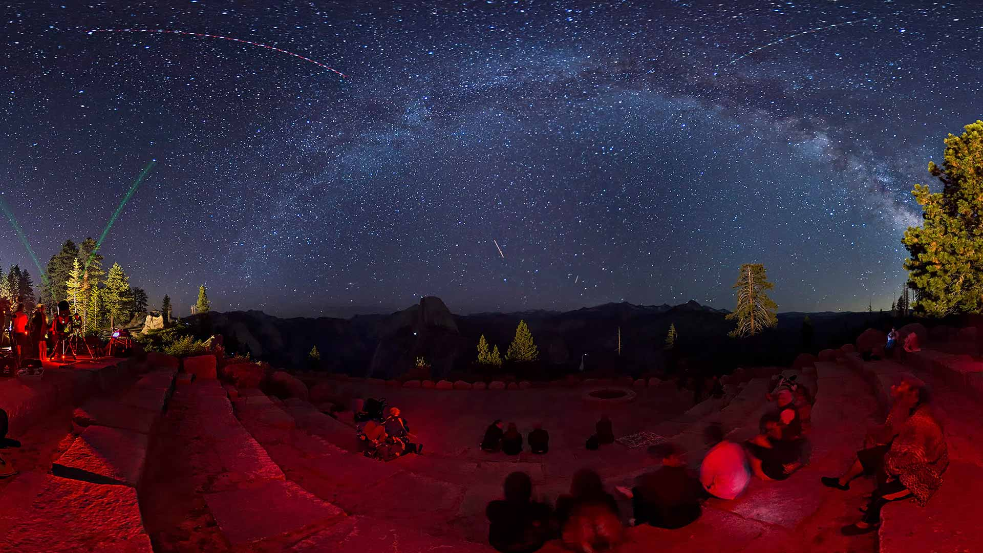 Panoramic view of the night sky over Yosemite National Park. The midnight blue sky is blanketed with stars. The ground is illuminated by a low red hue.